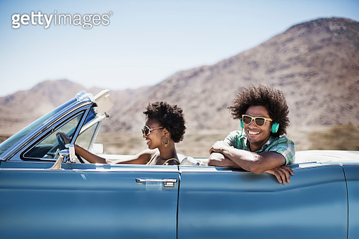 A young couple, man and woman in a pale blue convertible on the open road  - gettyimageskorea