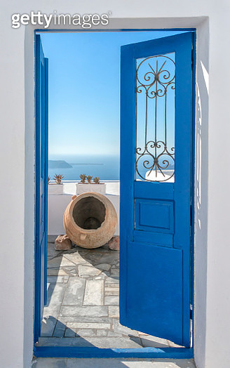 Bright sun and a traditional pot  seen throught  a beautiful blue door in Santorini,  in the background Caldera, - gettyimageskorea