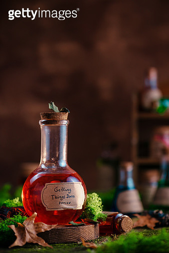 Red Getting Things Done potion on a background with moss and fallen leaves. Modern witchcraft and self-care concept with copy space. - gettyimageskorea
