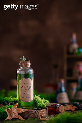 Green Snake Oil bottle on a background with moss and fallen leaves. Fake remedy, homeopathy, and unscientific medicine concept. - gettyimageskorea