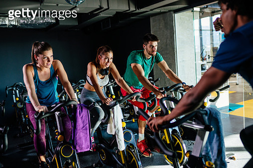 Group of young people exercising on exercise bikes at gym - gettyimageskorea