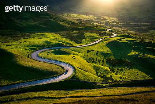 Car driving on a bendy road in glorious sunlight - gettyimageskorea