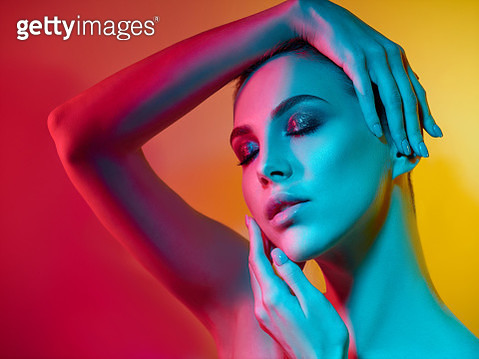 High Fashion model woman in colorful bright lights posing in studio - gettyimageskorea