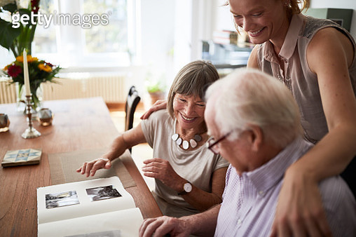 Family looking at photos in album - gettyimageskorea