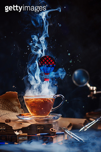 Hot air balloon above a steaming cup of tea. Metaphorical funny food photo on a dark background with copy space. - gettyimageskorea