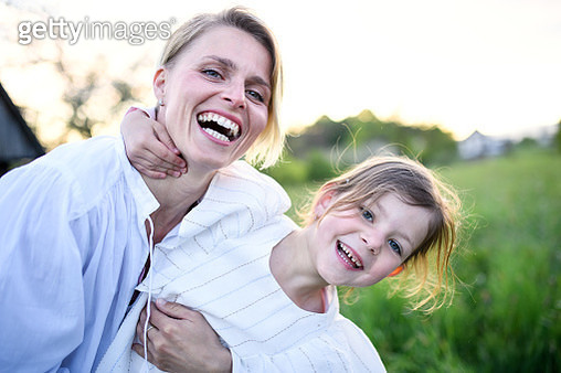 Portrait of mother with small daughter outdoors in spring nature, looking at camera. - gettyimageskorea