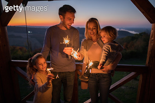 Cheerful family having fun with sparklers on a balcony in the evening. - gettyimageskorea