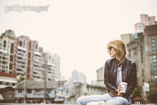 Beautiful woman sitting by the river holding cup of coffee and using phone - gettyimageskorea