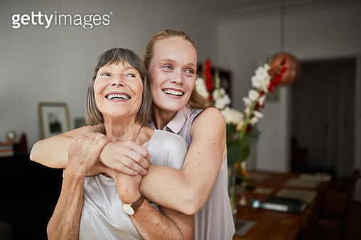 Cheerful mature woman embracing senior mother at home and looking away. Portrait of elderly mother and middle aged daughter smiling together. - gettyimageskorea