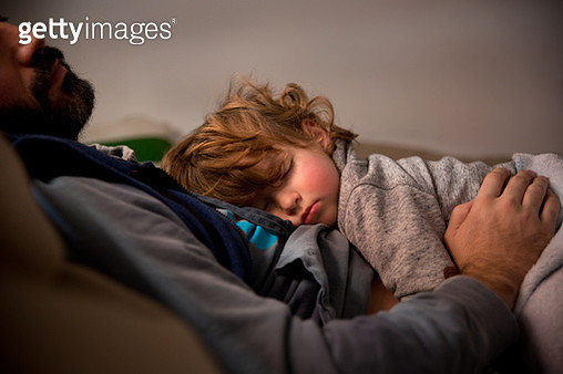 Toddler having a nap with dad in the sofa - gettyimageskorea