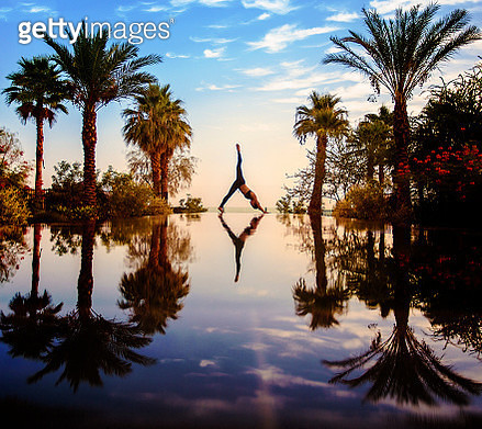 Young woman doing yoga beside swimming pool and palm trees - gettyimageskorea