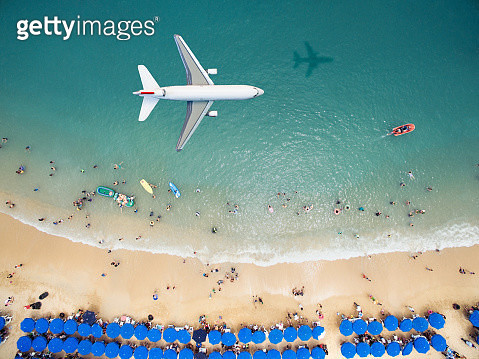 Airplane flying over a crowded beach - gettyimageskorea