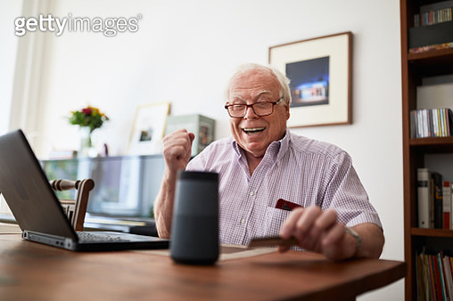 Smiling retired man purchasing online using wireless devices at home. Senior man doing online shopping using a credit card, laptop and digital voice assistant. - gettyimageskorea