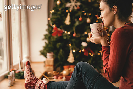 Young woman drinking tea by the Christmas tree - gettyimageskorea