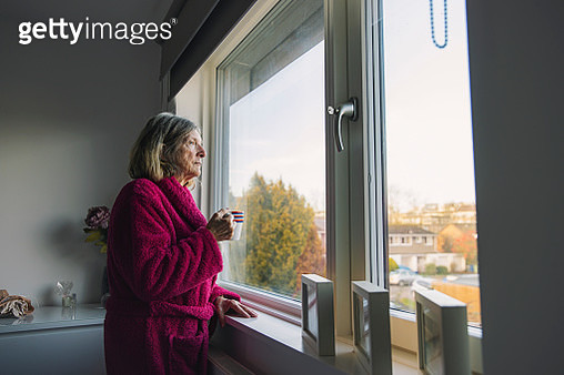 Sad senior woman looking out of the window - gettyimageskorea