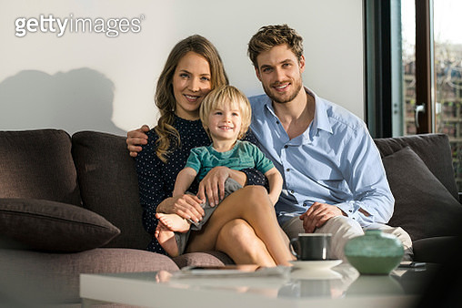 Portrait of smiling parents and son sitting on sofa at home - gettyimageskorea