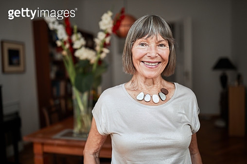 Portrait of a beautiful senior woman standing at home and looking at camera with a smile. Attractive retired female smiling at camera at home. - gettyimageskorea
