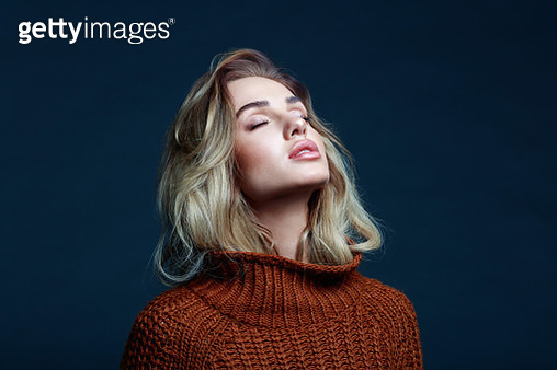 Fashion portrait of long hair blond young woman wearing brown sweater. Studio shot against black background. - gettyimageskorea