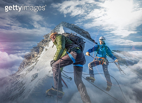 Two climber on a snowy slope preparing for the final ascent to the top - gettyimageskorea
