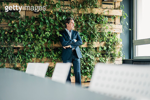 Businessman in green office looking out of window - gettyimageskorea