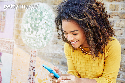 Woman smiling with smart phone - gettyimageskorea