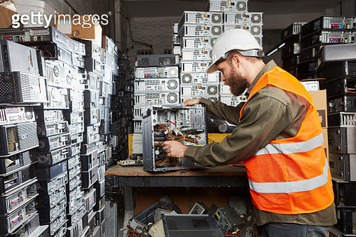Worker in computer recycling plant dismounting desktop pc - gettyimageskorea