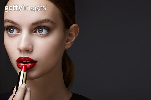 studio shot of a young beautiful brunette with a red lipstick in her hand in front of a dark background - gettyimageskorea