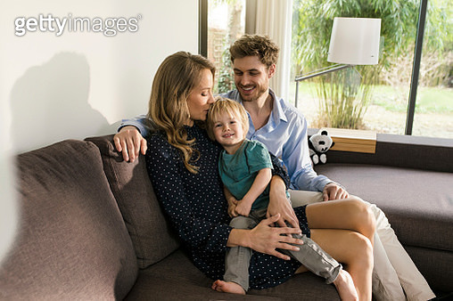 Happy parents sitting with son on sofa at home - gettyimageskorea