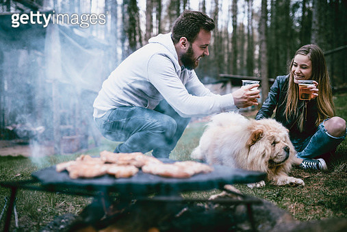 Couple Making A Barbecue And Playing With Pet Chow Chow While Drinking Beer - gettyimageskorea
