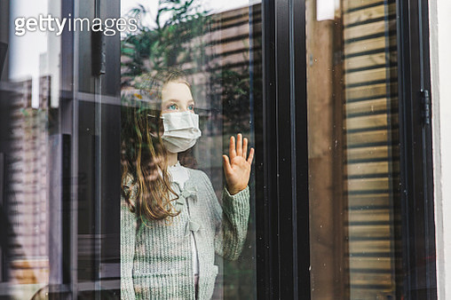 Young girl looking through window with mask - gettyimageskorea