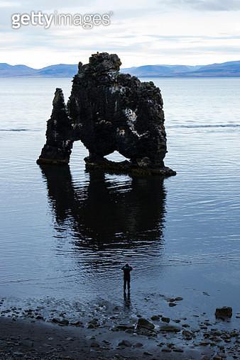 Hiker looking at coastal rock formation, Hvitserkur, Iceland - gettyimageskorea
