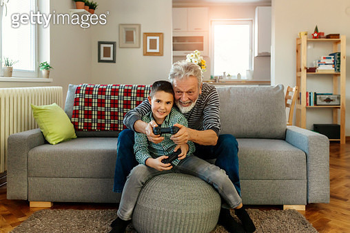 Grandfather and grandson having a great time together while playing video game console at home in the living room - gettyimageskorea