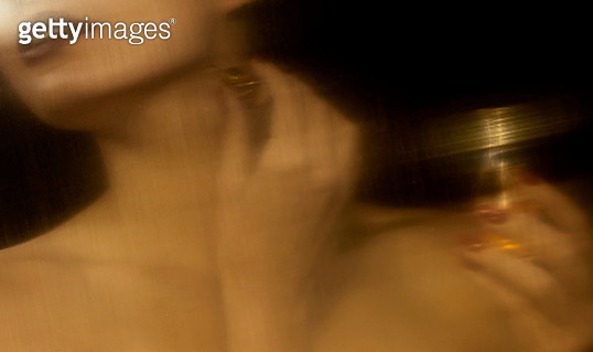 Close-up of woman applying perfume in a golden reflection - gettyimageskorea