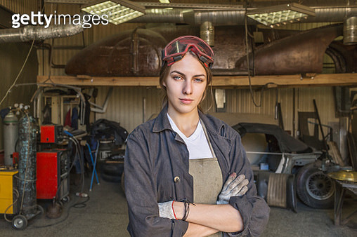 Portrait of confident female mechanic with arms crossed at garage - gettyimageskorea