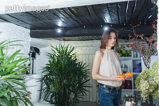 Female owner holding artificial pumpkins at decor shop - gettyimageskorea