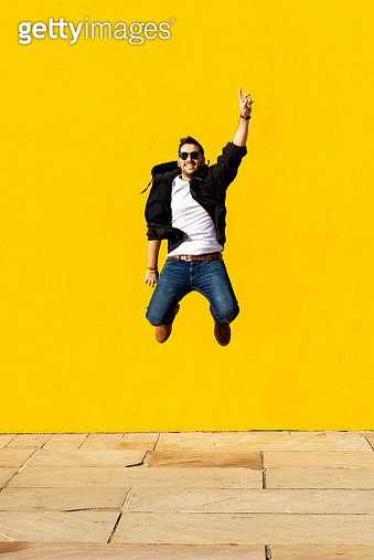 Young man with sunglasses jumping in front of a yellow wall. - gettyimageskorea