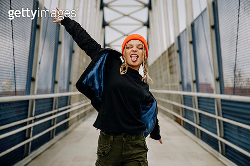 Happy young woman with eyes closed sticking out tongue while dancing on footbridge - gettyimageskorea