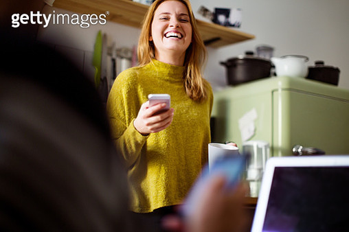 Young woman talking to man sitting in front and smiling. Cheerful female with mobile phone in kitchen. - gettyimageskorea