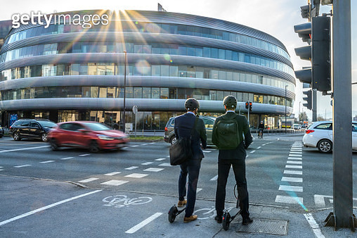 Two businessmen with electric push scooters waiting at a crossroads - gettyimageskorea
