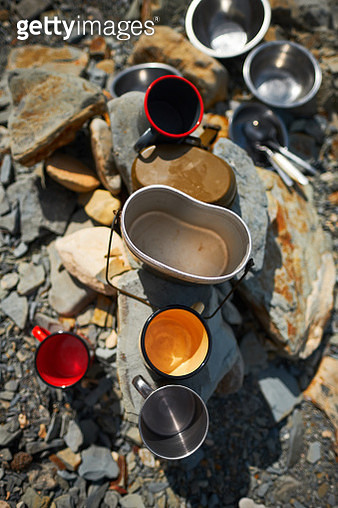 High Angle View Of Empty Coffee Cups On Rocks At Campsite - gettyimageskorea