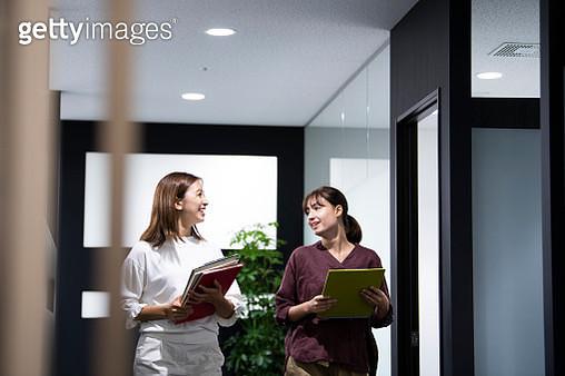 Two female colleagues walking in office corridor - gettyimageskorea