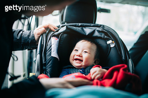Close up of mother taking care of cute smiling baby on car seat in car - gettyimageskorea