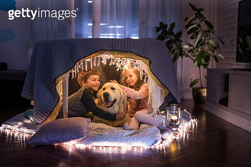 Cute little siblings enjoying with their dog in a tent at home. - gettyimageskorea