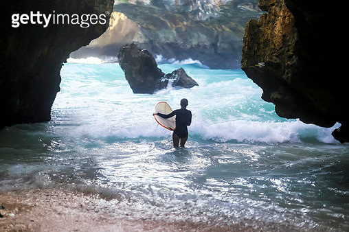 Indonesia, Bali, back view of surfer carrying surfboard - gettyimageskorea