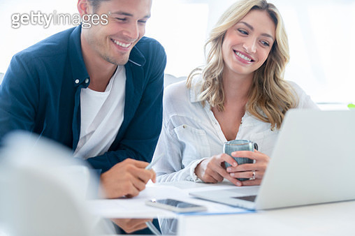 Young Couple working on their home finances and other paperwork. They are working at the dining room table. There is a laptop and mobile phone on the table along with some paperwork. They both look very happy and are laughing and smiling. - gettyimageskorea