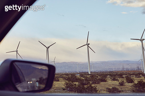 renewable and sustainable wind and solar power plant with dramatic sky taken from car window - gettyimageskorea