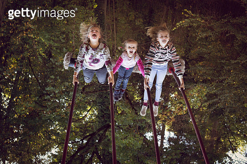Upside down image of three girls having fun on a rope swing in a forest playground - gettyimageskorea