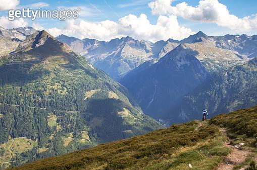 A person mountain biking in the Austrian Alps, Austria. - gettyimageskorea