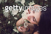 Beautiful young woman in a field of wild flowers. - gettyimageskorea