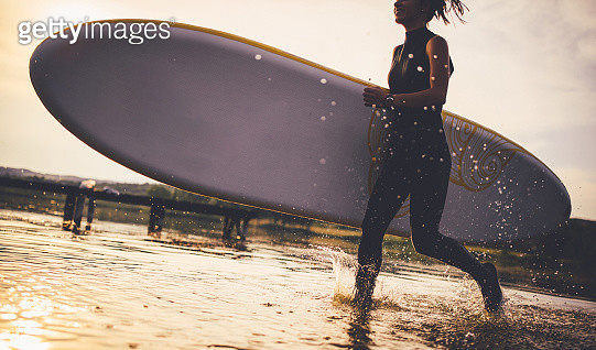 Surfer running into the water with surfboard - gettyimageskorea
